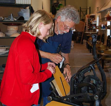 Eric Johnson of Iota Press helps book arts camp participant print her book cover with letterpress printing.